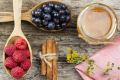 Raspberries and blueberries in spoons with pink napkin and a jar of honey with cinnamon on wooden background. Healthy eating Stock Image