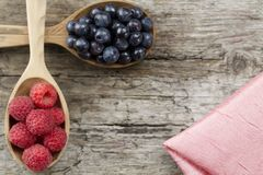 Raspberries and blueberries in spoons and pink napkin on wooden background. Healthy eating Royalty Free Stock Photos