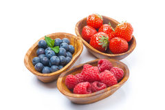 Raspberries, blueberries and strawberries in a wooden bowls. Isolated on white Royalty Free Stock Photo