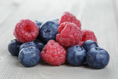 Raspberries and blueberries on wood table Stock Images
