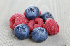 Raspberries and blueberries on wood table Stock Photo
