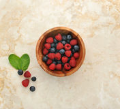 Raspberries and blueberries in a wooden bowl. Mint leaves and berries on a marble background. top view Stock Image