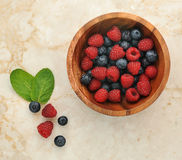 Raspberries and blueberries in a wooden bowl Stock Image