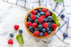 Raspberries and blueberries in a wooden bowl. Stock Images