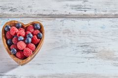 Raspberries and blueberries in a wooden heart-shaped dish. On white rustic wooden background. Top view, copy space stock image
