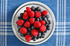 Raspberries and blueberry. On plate  with blue background Stock Photos