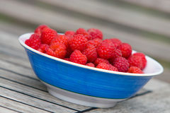 Raspberries in bowl. Fresh juicy raspberries in a blue and white bowl outdoors on a wooden table Royalty Free Stock Photography