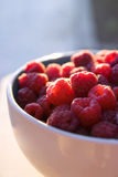 Raspberries bowl. A close-up shot of a bowl filled with freshly gathered red raspberries Stock Photo