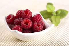 Raspberries in bowl on bamboo placemat Stock Photos