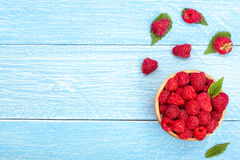 Raspberries in a bowl on the blue wooden background with copy space for your text. Top view Royalty Free Stock Photos