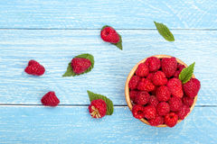 Raspberries in a bowl on the blue wooden background. Top view Royalty Free Stock Photo