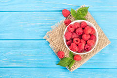 Raspberries in bowl. Full bowl of red raspberries with scattered leaves and berries on sacking and blue table, top view Stock Photos