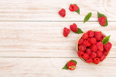 Raspberries in a bowl on the light wooden background with copy space for your text. Top view Stock Photography