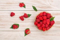 Raspberries in a bowl on the light wooden background. Top view.  Stock Images