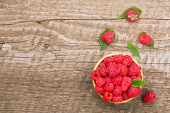 Raspberries in a bowl on the old wooden background with copy space for your text. Top view.  Royalty Free Stock Image