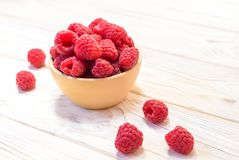Raspberries bowl on rustic wood background, top view with copy s. Pace. Organic berries on wooden table Stock Photo