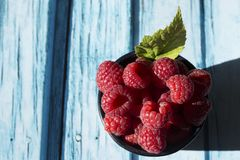 Raspberries bowl top view. With copy space on blue wooden background Stock Images