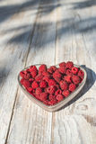 Raspberries in a bowl on wood Stock Image
