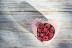 Raspberries in a bowl on wood Royalty Free Stock Image