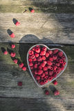 Raspberries in a bowl on wood Stock Photo