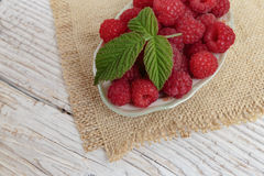 Raspberries in a bowl on a wooden table. Raspberries in a bowl on a wooden white table Stock Photography