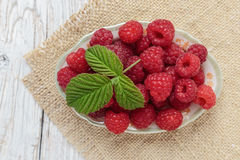 Raspberries in a bowl on a wooden white table Royalty Free Stock Photo