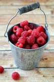 Raspberries in a bucket on the boards Stock Photo