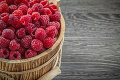 Raspberries in bucket on vintage wooden board horizontal image.  Royalty Free Stock Photography