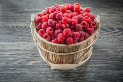 Raspberries in bucket on wooden board.  Royalty Free Stock Photography