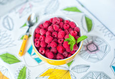 Raspberries in ceramic bowl. Ripe and tasty raspberries on colorful tablecloth. Raspberries in ceramic bowl. Top view. Ripe and tasty raspberries on a wooden Royalty Free Stock Photo