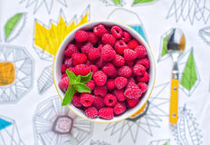 Raspberries in ceramic bowl. Ripe and tasty raspberries on colorful tablecloth. Raspberries in ceramic bowl. Top view. Ripe and tasty raspberries on a wooden Royalty Free Stock Image