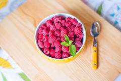 Raspberries in ceramic bowl. Ripe and tasty raspberries on a wooden background. Royalty Free Stock Images