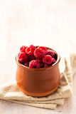 Raspberries in ceramic pot. Delicious pile of fresh raspberries in brown ceramic pot on napkin. Copy space Stock Photo