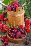 Raspberries, cherries and strawberries. In bowls on old rustic table Stock Images