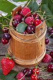 Raspberries, cherries and strawberries. On old rustic table Royalty Free Stock Image