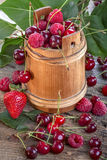Raspberries, cherries and strawberries. On old rustic table Stock Images