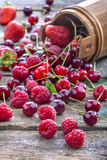 Raspberries, cherries and strawberries. Spilled on old rustic table Stock Photos