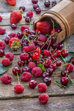 Raspberries, cherries and strawberries. Spilled on old rustic table Royalty Free Stock Images