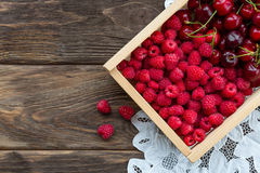 Raspberries and cherries in a wooden box on a wooden table. And a white lacy napkin near Royalty Free Stock Photos
