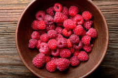 Raspberries in a clay bowl on a wooden table Royalty Free Stock Photo