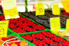 Raspberries in containers for sale at market place. Red raspberries in baskets for sale at market place Stock Photo