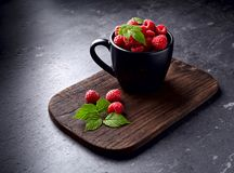 Raspberries in the cup on  a black background. Fresh raspberries with leaves in the cup on a black background Stock Image