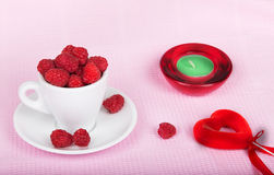 Raspberries in a cup, a candle and a heart. On a pink background Stock Photo