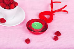 Raspberries in a cup, a candle and a heart. On a pink background Stock Photography