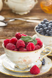 Raspberries  in cup. Red raspberries  in cup on wooden table Royalty Free Stock Image