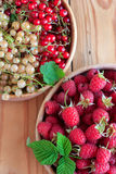 Raspberries and currants in wooden bowls. Ripe raspberries and currants in wooden bowls Royalty Free Stock Photos