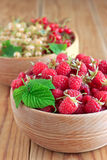 Raspberries and currants in wooden bowls. On the table Stock Images