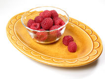 Raspberries in a Dish. A dish of red raspberries rests on a yellow plate Stock Photography