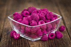 Wooden table with Dried Raspberries, selective focus. Raspberries dried as high detailed close-up shot on a vintage wooden table; selective focus Royalty Free Stock Images