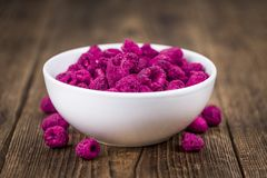 Wooden table with Dried Raspberries, selective focus. Raspberries dried as high detailed close-up shot on a vintage wooden table; selective focus Royalty Free Stock Photos